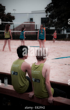 Two young people wait on the bench for their turn to play on a park volleyball court. - Stock Photo