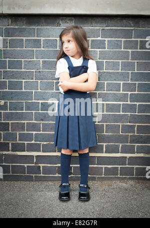 Portrait of girl in playground looking grumpy with arms folded - Stock Photo