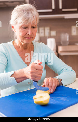 Woman using an ergonomic knife. - Stock Photo