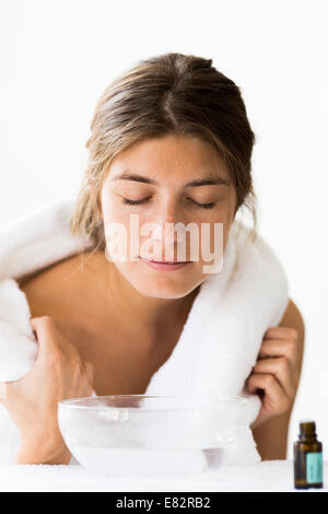 Woman treating a nasal congestion with an inhalation. - Stock Photo