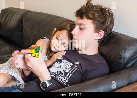 7 year old girl and teenage boy playing with a Rubik's cube®. - Stock Photo