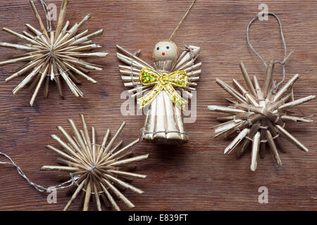 vintage toy angel figurine on weathered wooden table with straw snowflakes - Stock Photo