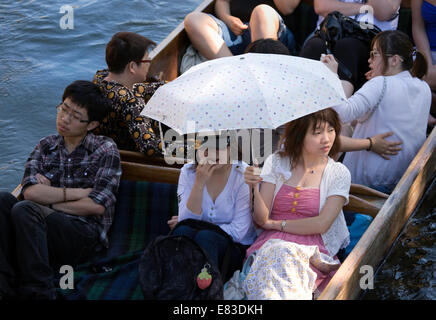 Japanese tourists in a punt punting on the River Cam, Cambridge, UK on a sunny summers day - Stock Photo