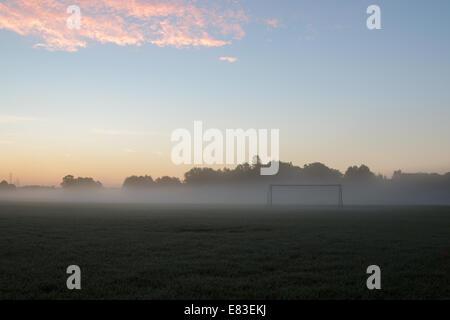 astel sunrise over early morning fog with soccer goal - Stock Photo