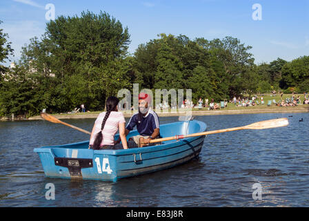 Young Sikh couple rowing on the boating lake in Regent's Park, London, England, UK - Stock Photo