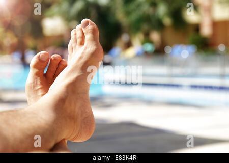 Sunbathing by swimming pool - Stock Photo