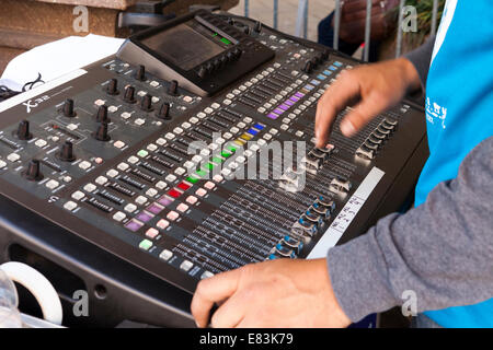 Technician at work on audio mixing console - USA - Stock Photo