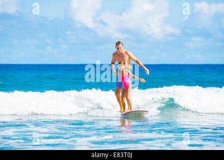 Father and Daughter Surfing Together Catching Wave, Summer Lifestyle Family Concept - Stock Photo