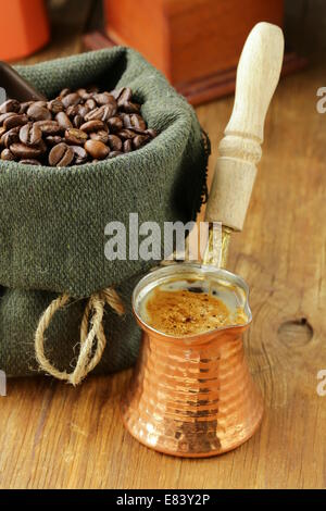 Still life coffee beans in a bag and copper coffee pot - Stock Photo