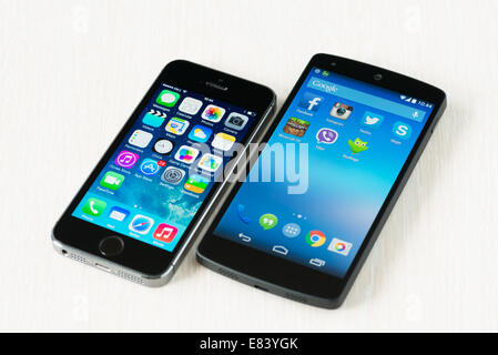 Close-up shot of brand new Apple iPhone 5S and Google Nexus 5 smartphones lying on a desk. - Stock Photo