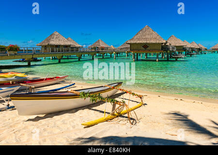Outrigger boats on the beach, overwater bungalows, Bora Bora, French Polynesia - Stock Photo