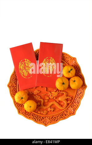 Chinese New Year festival tangerines and red packets on plate - Stock Photo