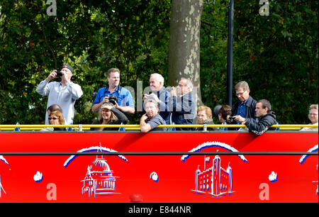 London, England, UK. People taking photos on the top deck of an open tourist bus - Stock Photo