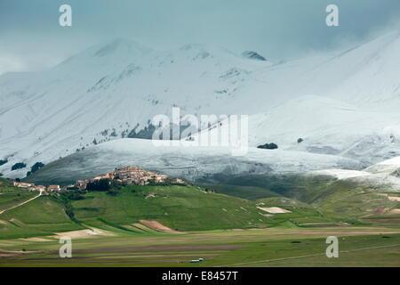 Castelluccio di Norcia and the Piano Grande in late spring, with snowy mountains; Monti Sibillini National Park, - Stock Photo