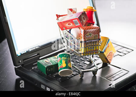 Miniature shopping cart with food packaging and laptop as a symbol for online shopping. - Stock Photo