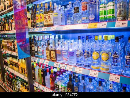 Shelf with a large selection of liquors in the supermarket. - Stock Photo