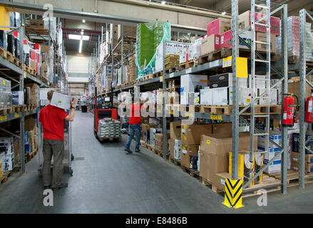Two workers in a warehouse with high shelves. - Stock Photo
