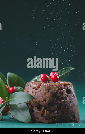 Christmas pudding dressed with winter berries and leaves and dusted with icing sugar - Stock Photo