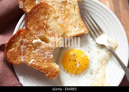 Two slices of buttered toast with a fried egg on a plate with a fork - Stock Photo