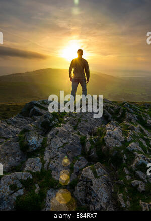 A lone figure watching the sunrise from a hill top vantage point. - Stock Photo