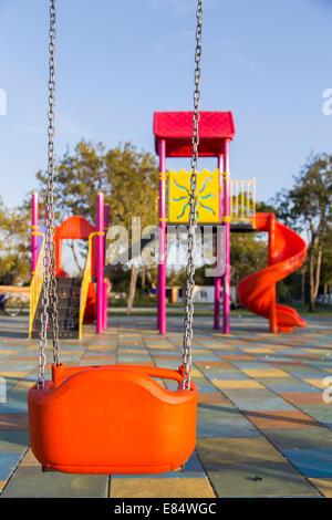 Swing seat on children playground without children - Stock Photo