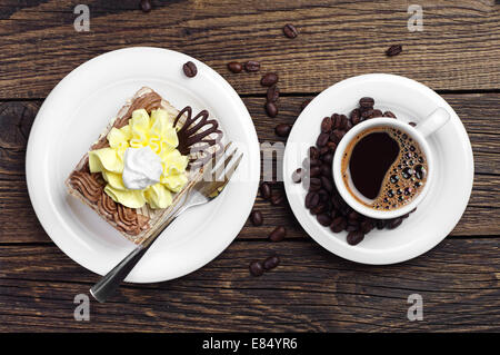 Cake and cup of coffee on wooden table viewed from above - Stock Photo