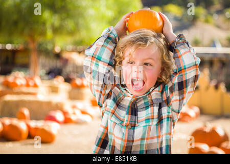 Adorable Little Boy Sitting and Holding His Pumpkin in a Rustic Ranch Setting at the Pumpkin Patch. - Stock Photo