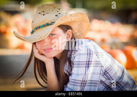 Pretty Preteen Girl Wearing Cowboy Hat Portrait at the Pumpkin Patch in a Rustic Setting. - Stock Photo