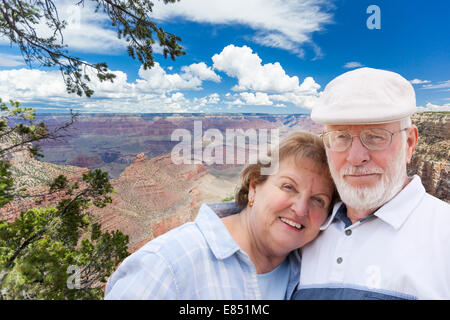 Happy, Hugging Senior Couple Posing on the Edge of The Grand Canyon. - Stock Photo