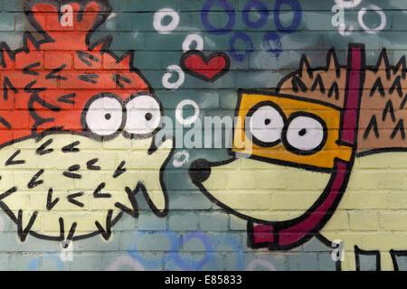 Spiny fish figure kissing a hedgehog figure wearing goggles, mural, North Rhine-Westphalia, Germany - Stock Photo