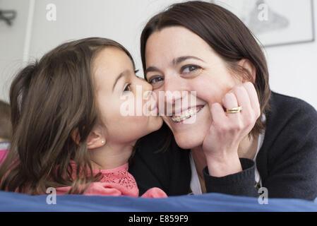 Little girl kissing mother's cheek - Stock Photo