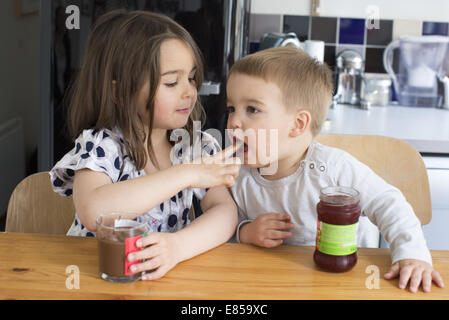 Young siblings tasting contents of jars with their fingers