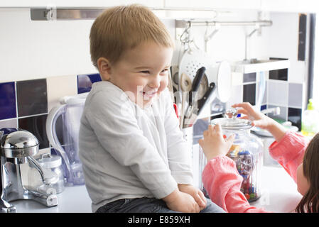Toddler boy sitting on kitchen counter, smiling as sister reaches for candy jar - Stock Photo