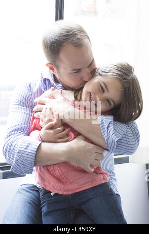 Father holding daughter on his lap, kissing her cheek - Stock Photo