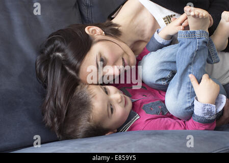 Mother and young son relaxing together on sofa - Stock Photo