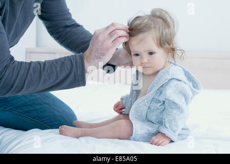 Father fixing baby girl's hair, cropped - Stock Photo