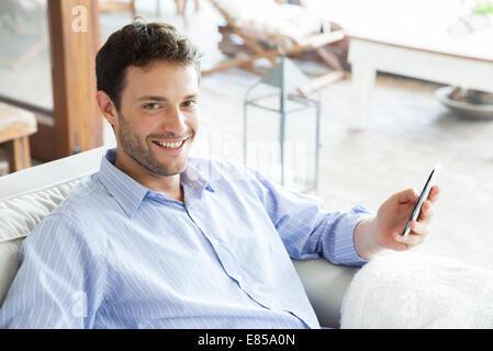 Man using smartphone, smiling - Stock Photo