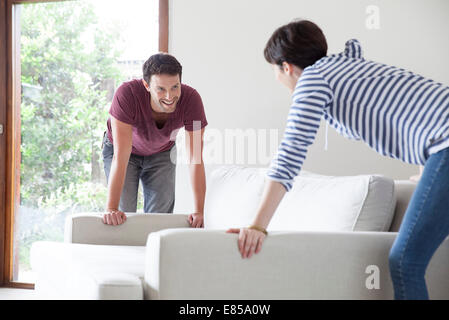 Couple moving sofa together - Stock Photo