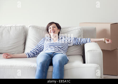 Woman resting on sofa while moving house - Stock Photo