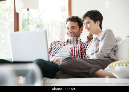 Couple relaxing together on sofa with laptop computer - Stock Photo
