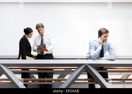Businessman talking on cell phone, colleagues using digital tablet nearby - Stock Photo