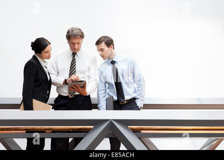 Executives looking at digital tablet together - Stock Photo