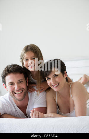Parents and daughter lying on bed together, portrait - Stock Photo
