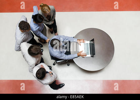 Businessman using laptop computer with colleagues standing by watching - Stock Photo