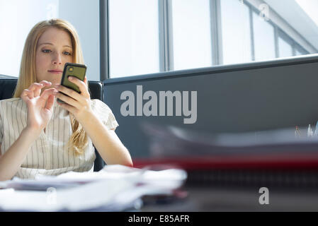 Office worker text messaging at desk - Stock Photo