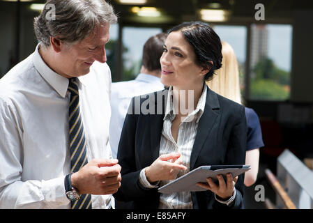 Business professionals marvelling at features of new digital tablet - Stock Photo