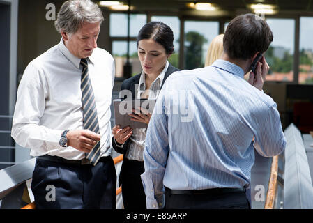 Businesswoman showing colleague digital tablet - Stock Photo
