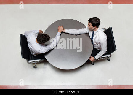 Businessman defeats colleague at arm wrestling match - Stock Photo