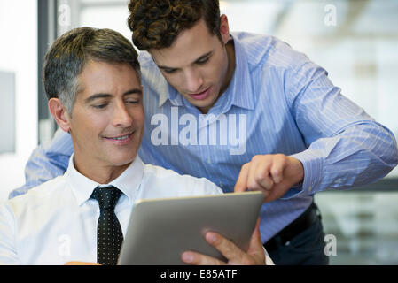 Assistant helping executive use digital tablet - Stock Photo
