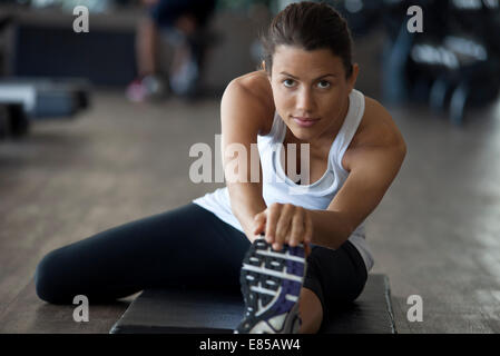 Woman at gym warming up with leg stretches - Stock Photo